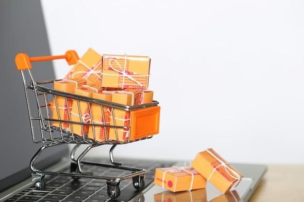 Brązowe pudełko paczek i miniaturowy model koszyka na klawiaturze komputera Premium Zdjęcia