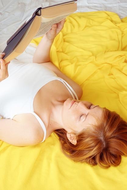 Brązowowłosa Kaukaska Dziewczyna W Białej Koszulce Czyta Książkę Podczas Leżenia. Premium Zdjęcia