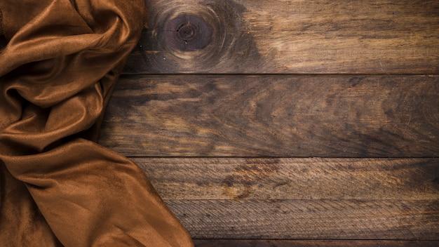 Brązowy jedwabny materiał na wyblakły drewniany stół Darmowe Zdjęcia