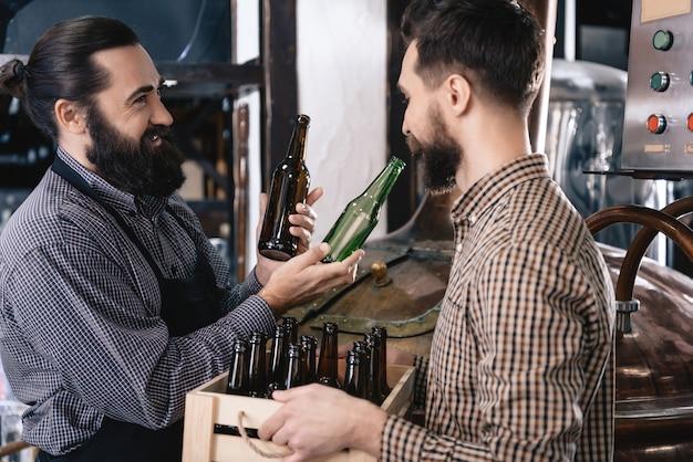 Brewer Wybiera Brązową I Zieloną Butelkę Na Piwo Ale. Premium Zdjęcia
