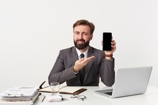 Brodaty Biznesmen, Najwyższy Menadżer Siedzi Przy Biurku W Biurze, Patrzy Na Aparat I Chce Zwrócić Twoją Uwagę Na Swojego Smartfona, Ubrany W Drogi Garnitur Z Krawatem. Pojedynczo Na Białej ścianie. Darmowe Zdjęcia