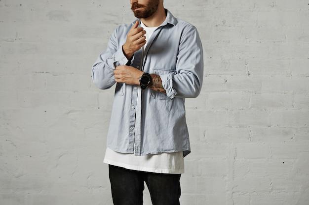 Brodaty Hipster Rozpinający I Podwijający Drugi Rękaw Swojej Zwyczajnej Wyblakłej, Niebieskiej Dżinsowej Koszuli Z Białymi ścianami Darmowe Zdjęcia