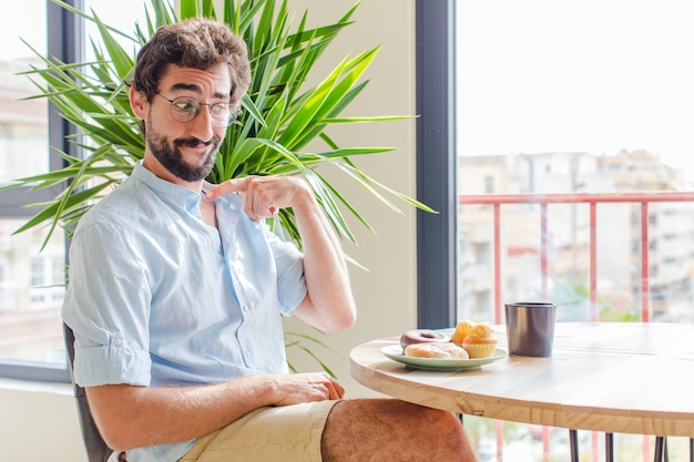 Brodaty Mężczyzna Czuje Się Zestresowany, Niespokojny, Zmęczony I Sfrustrowany, Ciągnie Za Szyję Koszuli, Wygląda Na Sfrustrowanego Problemem Premium Zdjęcia