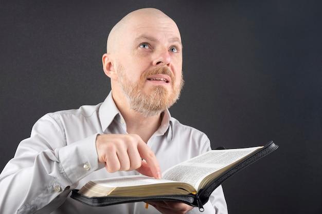 Brodaty Mężczyzna Czytający Biblię Wskazuje Palcem Na Tekst I Podnosi Wzrok Premium Zdjęcia