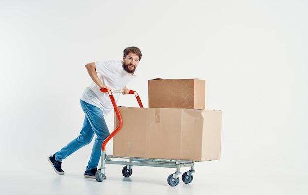 Brodaty Mężczyzna Kurier Z Kartonami Na Wózku Cargo Premium Zdjęcia