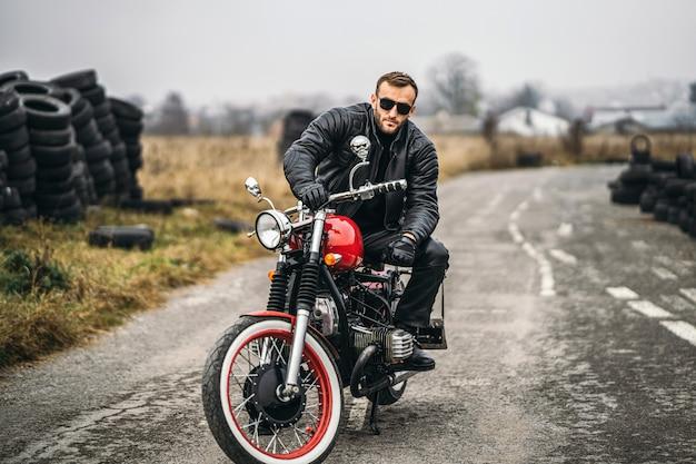Brodaty Mężczyzna Patrzeje Kamerę W Okularach Przeciwsłonecznych I Skórzanej Kurtce Podczas Gdy Siedzący Na Motocyklu Na Drodze. Za Nim Jest Rząd Opon Premium Zdjęcia