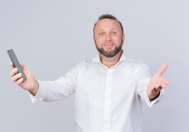 Brodaty Mężczyzna Ubrany W Białą Koszulę, Trzymając Smartfon Robi Powitalny Gest Ręką Uśmiechnięty Stojący Nad Białą ścianą Darmowe Zdjęcia