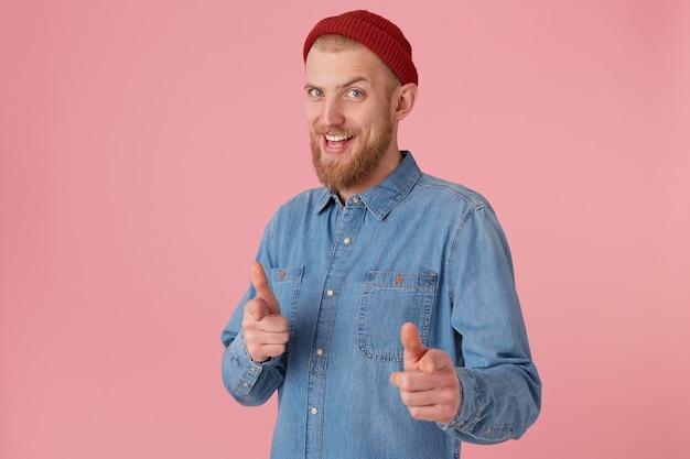 Brodaty Mężczyzna W Czerwonej Czapce Z Modnej Dżinsowej Koszuli, Zachęca, Uśmiecha Się, Wykonuje Gest Wsparcia, Wskazując W Przód Darmowe Zdjęcia