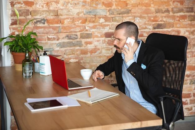 Brodaty Mężczyzna W Kurtce I Bez Spodni Pracuje W Domu W Izolacji. Domowe Biuro Darmowe Zdjęcia