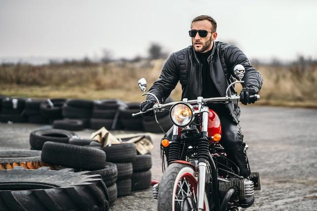 Brodaty Mężczyzna W Okularach Przeciwsłonecznych I Skórzanej Kurtce, Siedząc Na Czerwonym Motocyklu I Patrząc Na Drodze. Premium Zdjęcia