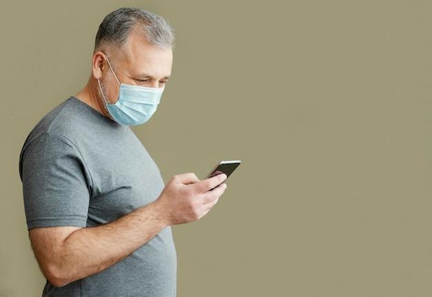 Brodaty Mężczyzna Z Maską Chirurgiczną Przy Użyciu Telefonu Darmowe Zdjęcia