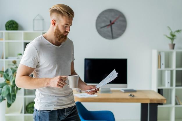 Brodaty Młody Biznesmen Pracujący W Nowoczesnym Biurze. Mężczyzna Ubrany W Białą Koszulkę I Robienie Notatek Na Dokumentach. Premium Zdjęcia