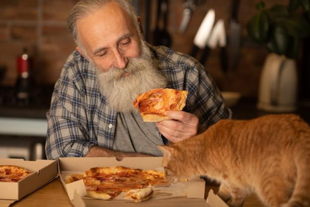 Brodaty Starszy Mężczyzna Z Jego Czerwonym Kotem Jedzenia Pizzy W Kuchni W Domu. Premium Zdjęcia