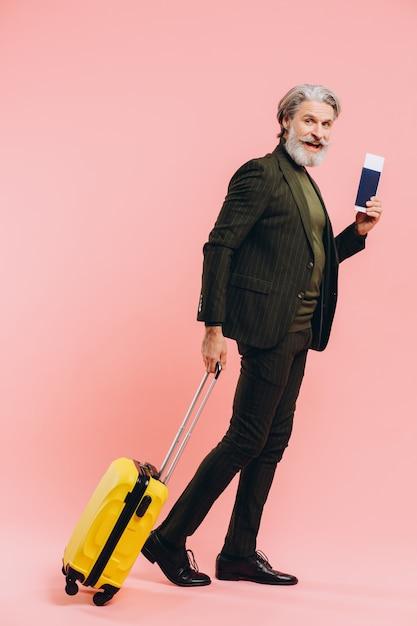 Brodaty Stylowy Mężczyzna W średnim Wieku Z żółtą Walizką I Paszportem Z Różowym Biletem. Premium Zdjęcia