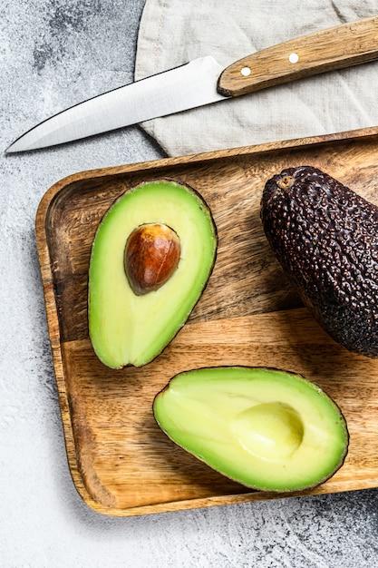 Brown dojrzałe avocado połówki na drewnianej ciapanie desce. Premium Zdjęcia