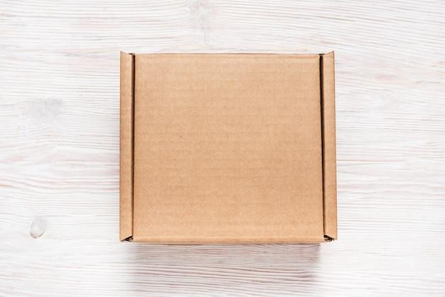 Brown Karton, Wyśmiewa Up, Na Drewnianym Tle Premium Zdjęcia