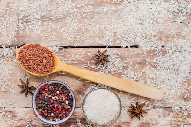 Brown Ryż W Drewnianej łyżce Z Peppercorn I Gwiazdowym Anyżem Na Nieociosanym Drewnianym Tle Selekcyjna Ostrość Darmowe Zdjęcia