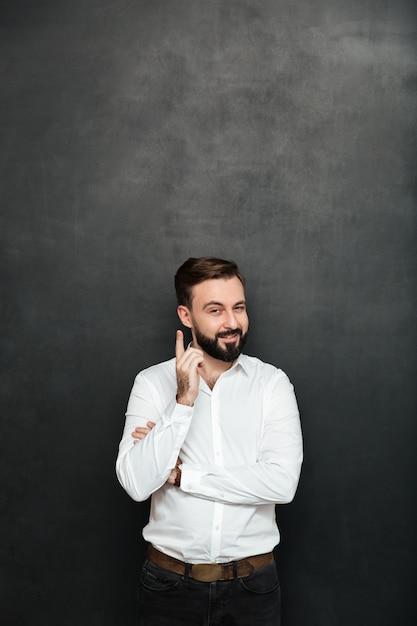 Brunetka Biznesmen Pozuje Na Kamerze Z Chytrym Szczęśliwym Spojrzeniem, Wskazuje Palec Wskazującego, Jakby Wiedział Coś Nad Ciemnoszarym Darmowe Zdjęcia
