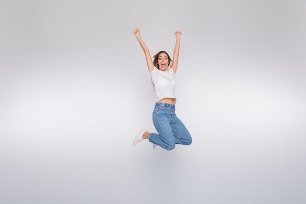 Brunetka Dama W Okularach Pozowanie I Skoki Na Białej ścianie Premium Zdjęcia