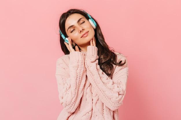 Brunetka Dziewczyna Z Przyjemnością Słucha Muzyki Na Słuchawkach. Kobieta W Różowym Stroju Uśmiechnięta Na Na Białym Tle. Darmowe Zdjęcia
