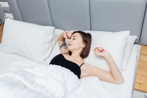 Brunetka Kobieta Leży Na łóżku Rano Obudzić, Rozciągając Ręce I Ciało Darmowe Zdjęcia