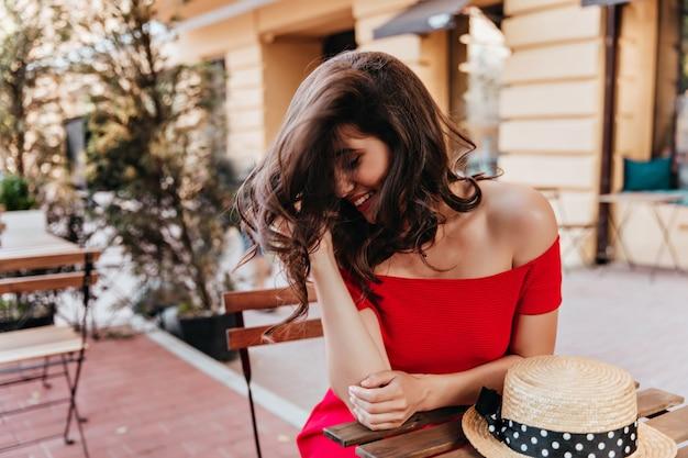 Brunetka Kobieta Pozuje Z Nieśmiałym Uśmiechem W Restauracji Na świeżym Powietrzu. Portret Blithesome Dziewczynka Kaukaski Siedzi Przy Stole Z Kapeluszem Na To. Darmowe Zdjęcia