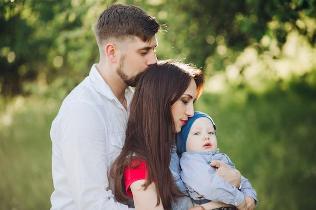 Brunetka Mąż Całuje Swoją żonę, Kobieta Trzyma Małego Syna I ściska Premium Zdjęcia