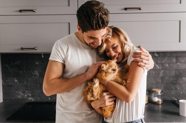 Brunetka Mężczyzna Patrząc Na Swojego Kota I Obejmującą żonę. Kryty Portret Szczęśliwej Rodziny Pozuje Ze Zwierzakiem. Darmowe Zdjęcia