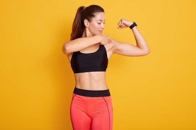 Brunetka Młoda Kobieta Ubiera Czarny Top I Legginsy, Wskazując Na Biceps. Premium Zdjęcia