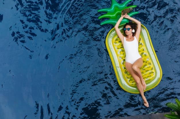 Brunetka Młoda Kobieta W Białym Stroju Kąpielowym, Słuchanie Muzyki Podczas Pływania W Basenie. Plenerowe Zdjęcie Czarującej Ciemnowłosej Pani Bawiącej Się W Letnim Kurorcie. Darmowe Zdjęcia
