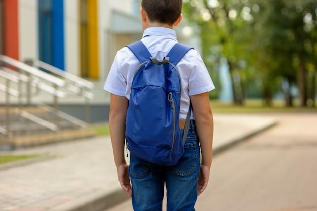 Brunetka Uczennica W Białej Koszuli I Niebieskim Plecaku Idzie Do Szkoły Premium Zdjęcia