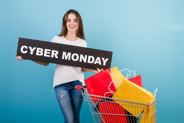 Brunetki kobieta z wózek na zakupy pełno kolorowe czerwone i żółte papierowe torby i cyber poniedziałku podpisujemy odosobnionego nadmiernego błękit Premium Zdjęcia