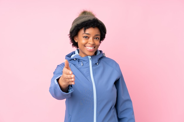 Brunetki kobieta z zima kapeluszem nad odosobnionym błękitnym tłem Premium Zdjęcia