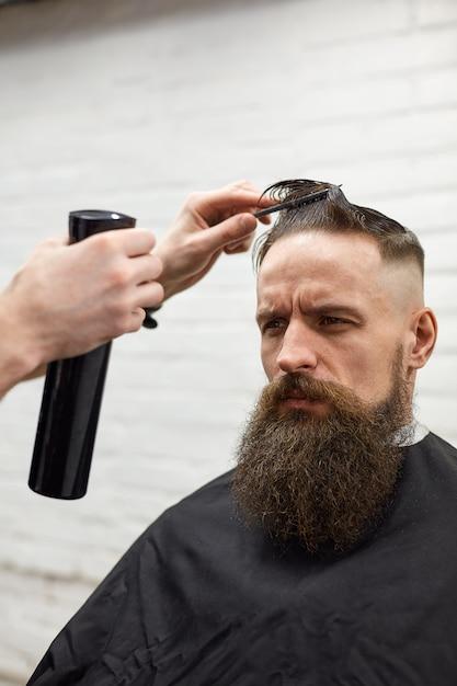 Brutalny Facet W Nowoczesnym Sklepie Fryzjerskim. Fryzjer Sprawia, że Fryzura Jest Mężczyzną Z Długą Brodą. Mistrz Fryzjer Robi Fryzurę Maszynką Do Strzyżenia Włosów Premium Zdjęcia