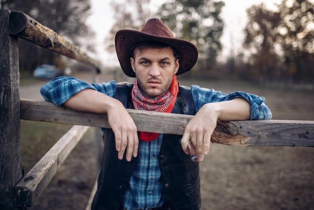 Brutalny Kowboj Pozuje W Zagrodzie Dla Koni Premium Zdjęcia
