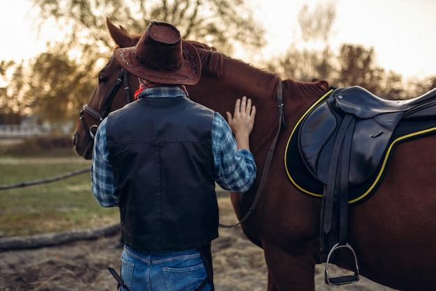 Brutalny Kowboj Pozuje Z Koniem, Dziki Zachód Premium Zdjęcia