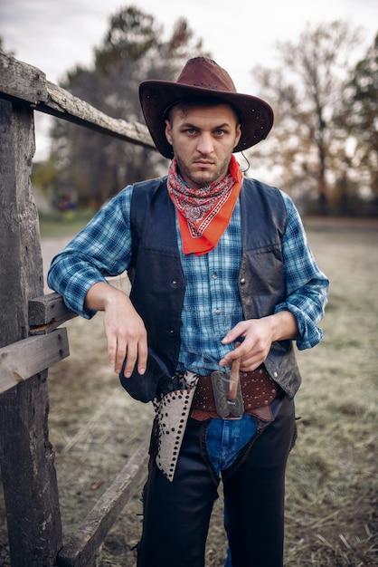 Brutalny Kowboj Z Cygarem W Zagrodzie Dla Koni Premium Zdjęcia