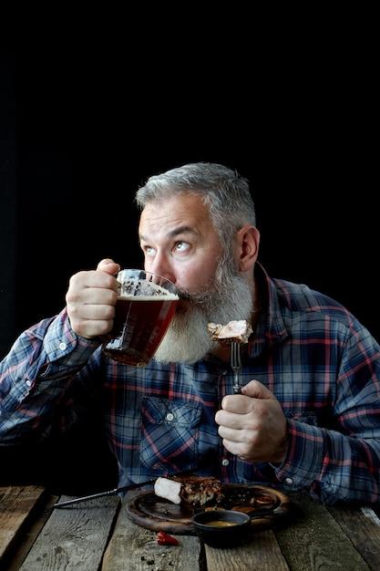 Brutalny siwy dorosły mężczyzna oszalały na punkcie steku i piwa z musztardy, wakacji, festiwalu, oktoberfest lub dnia świętego patryka Premium Zdjęcia