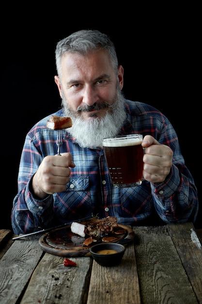 Brutalny siwy dorosły mężczyzna z brodą zjada stek musztardy i pije piwo, święto, festiwal, oktoberfest lub dzień świętego patryka Premium Zdjęcia