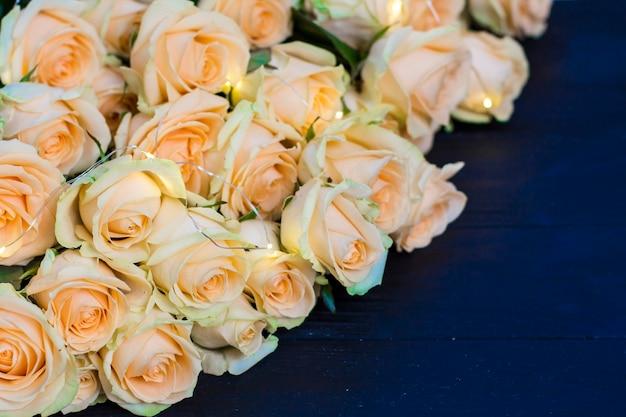 Brzoskwini Róże Na Drewnianym Czarnym Tle Premium Zdjęcia