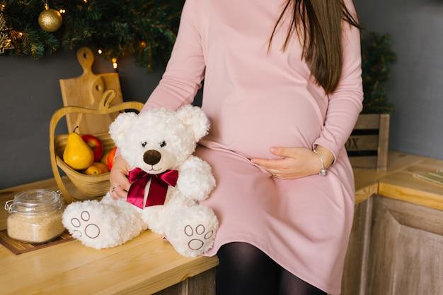 Brzuch kobiety w ciąży w różowej sukience z dzianiny, trzyma dłoń na brzuchu, siedząc obok miękkiego zabawkowego niedźwiedzia polarnego ze szkarłatną kokardą Premium Zdjęcia