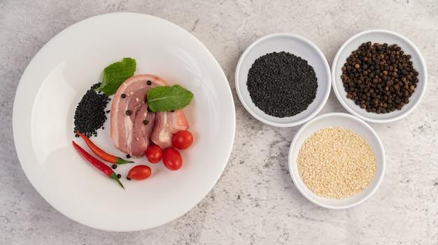 Brzuch Wieprzowy Pokrojony Na Białej Tablicy Z Ziarnami Pieprzu I Pomidorami. Darmowe Zdjęcia
