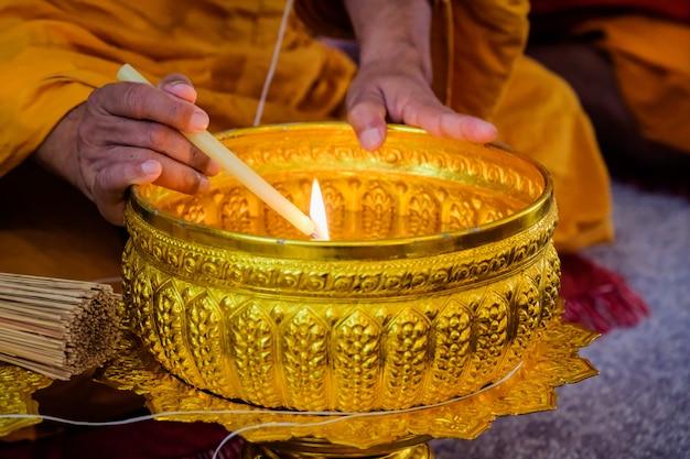 Budda pali świece, aby stworzyć święconą wodę. Premium Zdjęcia