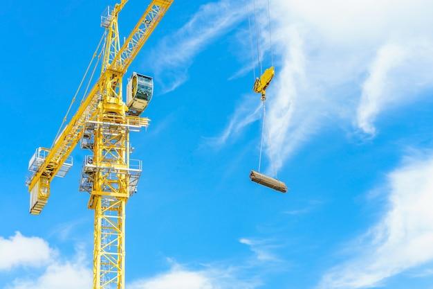 Budowa żurawie i wieżowiec w budowie przeciw niebieskiemu niebu. Premium Zdjęcia