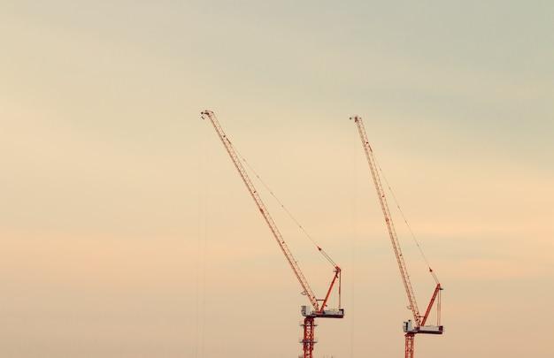 Budowa żurawie na zmierzchu nieba tle. Premium Zdjęcia