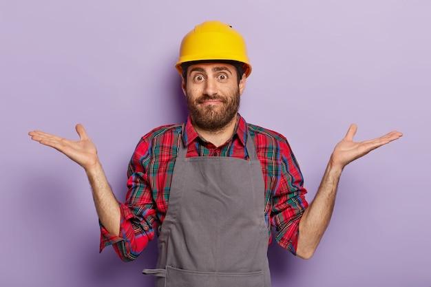 Budowniczy Mężczyzna Nosi Hełm I Fartuch Budowlany, Rozkłada Ręce W Dezorientującym Geście Darmowe Zdjęcia
