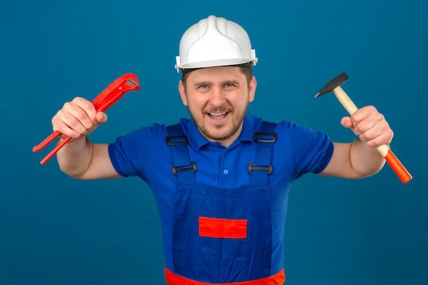 Budowniczy Mężczyzna Ubrany W Mundur Konstrukcyjny I Hełm Ochronny Stojący Z Podniesionymi Rękami Trzymającymi Młotek I Klucz Nastawny Zagrażający Pozie, Bawiąc Się Na Odizolowanej Niebieskiej ścianie Darmowe Zdjęcia