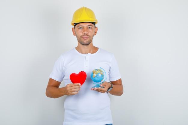Budowniczy Mężczyzna W Białej Koszulce, Hełm Trzymający Czerwone Serce I Kula Ziemska, Widok Z Przodu. Darmowe Zdjęcia