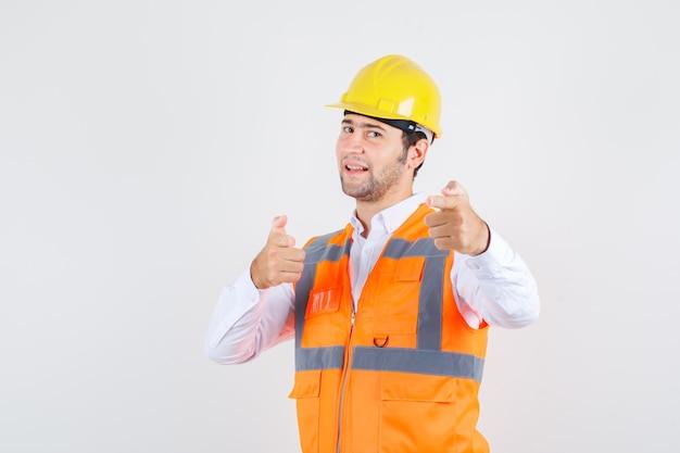 Budowniczy Mężczyzna Wskazujący Na Zaproszenie W Koszuli, Mundurze I Wyglądający Pozytywnie. Przedni Widok. Darmowe Zdjęcia