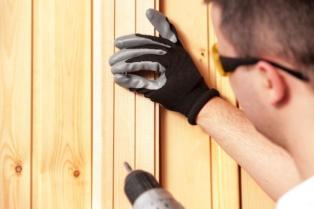 Budowniczy Trzyma W Ręku Elektryczny śrubokręt Na Tle Betonowej ściany. Premium Zdjęcia